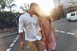 She is his universe. Beautiful young couple holding hands and smiling while walking through the city street