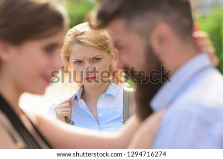 She is obviously jealous. Bearded man cheating his girlfriend with another woman. Unhappy girl feeling jealous. Romantic couple of man and woman dating. Jealous woman look at couple in love on street. Stock photo ©