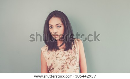She is reading your face. Vintage, retro style of portrait of Asian woman in pink vintage dress on blue - green background.