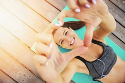 She loves sport. Top view of beautiful and young woman in sports clothing making heart with her hands and smiling while laying on yoga mat on wooden pier.