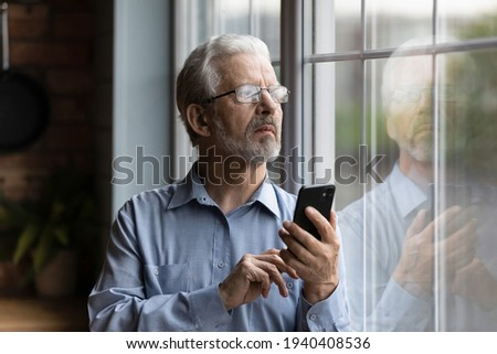 She should be back by now. Worried older man husband look at window wait for wife delayed to go back home hold phone make call. Nervous retired father feel distressed for grown child dial cell number Сток-фото ©