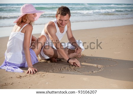 She watches, as he paints love on the sand.