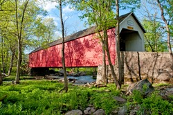 Sheard's Mill historic covered bridge, in Bucks County, Pennsylvania, spans a small stream.  This photo was taken in the summer when the surrounding landscape was lush and green with blue sky.