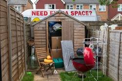 Shed overflowing with clutter, van in the background with decal saying Need Extra Space?
