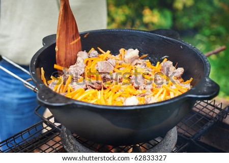Sheep meat fried with onions and carrots in oil in a cauldron