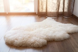 Sheep skin on the laminate floor in the room. Cozy place near the window. Sunny day.