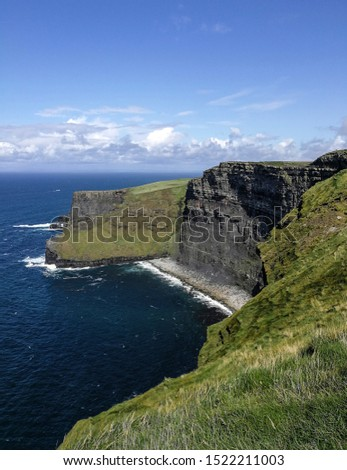 Sheer cliff edge & secluded beach at the famous Cliffs of Moher, County Clare, Ireland. With blue sky, ocean and clouds. #1522211003