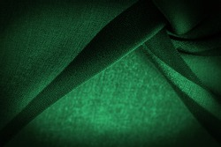 Sheer dark green chiffon silk, Emerald abstract background. Green fabric closeup. - it is a soft transparent fabric with a slight roughness (matte, crepe) due to the use of twisted yarn. texture