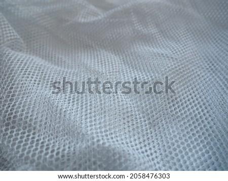 Sheer white net-like tulle. Mesh fabric is wrinkled or folded carelessly. Close-up. White - blue veil or muslin