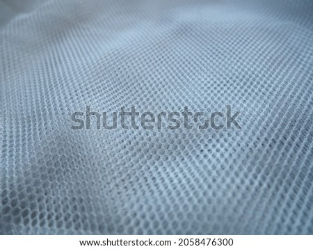 Sheer white net-like tulle. Mesh fabric is wrinkled or folded carelessly. Close-up. White veil or muslin. Curtain with holes of different sizes close-up