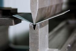 Sheet metal bending on a hydraulic bending machine. Metal part after bending.