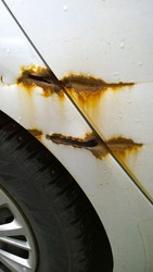 Sheet metal corrosion and scratches car body. Rusty steel surface and damaged texture. Stops and prevents rust concept. Protection and painting auto. Professional paint and repair. Messy. Vertical.