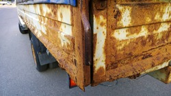 Sheet metal corrosion of body of an old truck. Rusty surface, background and damaged texture from road salt and reagents. Protection and Professional paintwork concept. Dirty Cargo bed.