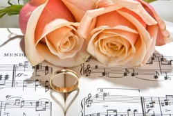 Sheet music of the Wedding March with roses and rings