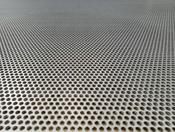 Sheet of a perforated stainless steel ideal for industrial brochures background
