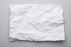Sheet of crumpled paper on grey background, top view