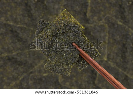 Sheet of dried crispy seaweed with chopsticks on seaweed background