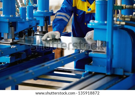 Sheet of metal and hands of worker who works on press Сток-фото ©