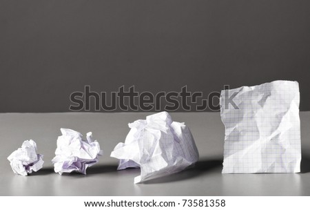 sheet of paper and crumpled wads on table.