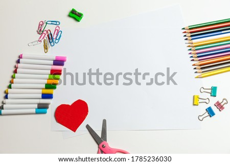 Sheet of paper, crayons, pencils, scissors and supplies on a white table. Children's art, Craft for kids or Preparing a child for school. Desktop for creativity Foto stock ©