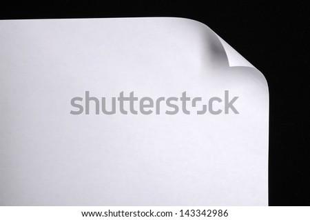 Sheet of paper folded over black background