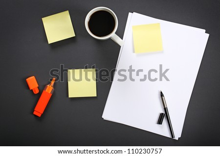 Sheet of paper, pen, cup of coffee and other office equipment on black office table.