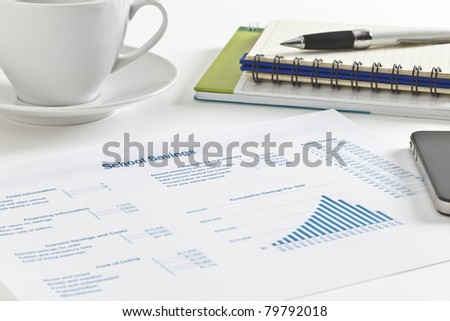 Sheet of paper with figures, tables and graph, small notebook and pen, cell phone and a cup of tea