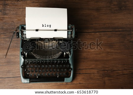 Sheet of paper with word BLOG in typewriter on wooden background #653618770