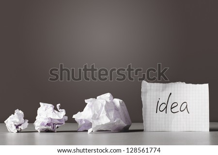 sheet of paper with word idea and crumpled wads on table.