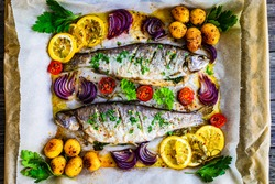 Sheet pan dinner - roasted whole trouts with lemon ,rosemary, tomatoes, red onion and potatoes on cooking pan on wooden table