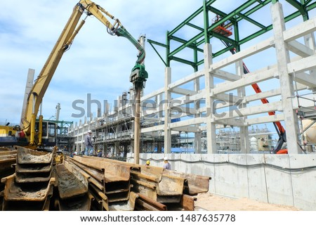Sheet pile cofferdam driven machine at the construction site. The machine drove the sheet pile to the earth using vibrated hydraulic arm.