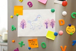 Sheets of paper, child's drawing and magnets on refrigerator door indoors