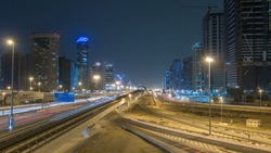 Sheikh Zayed road traffic night timelapse with Dubai marina and jlt skyscrapers. Line of Dubai Metro as world's longest fully automated metro network (75 km). Top view from bridge. Dubai, UAE