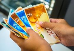 Shekel banknotes - hands holding Israeli currency