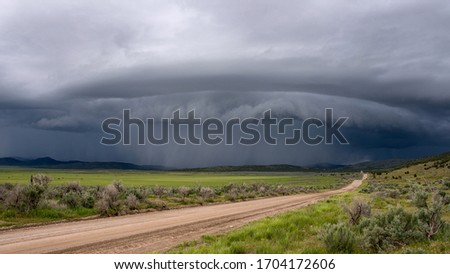 Shelf cloud storm moving over the landscape with road leading of into the distance towards the storm. Foto stock ©