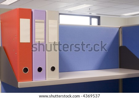 Shelf in an office cubicle with some files
