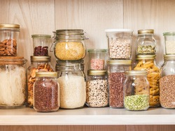 Shelf in the kitchen with various cereals and seeds - peas split, sunflower and pumpkin seeds, beans, rice, pasta, oatmeal, couscous, lentils,  bulgur in glass jars