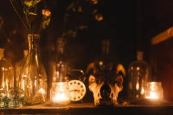 Shelf of alchemist jars of medicine potions skull goat skull. Ancient mystery magic mystic occult ritual. Candles old antique witch scary halloween witcher sorcerer wizard spiritism texture