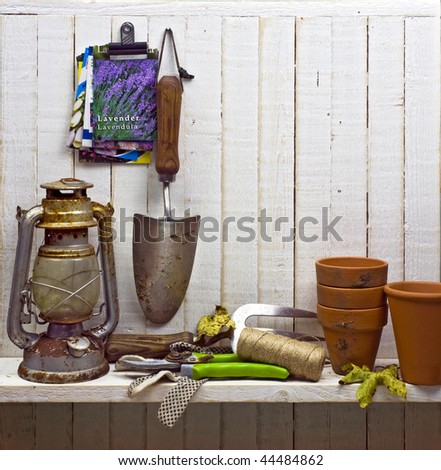 shelf of junk and gardening implements in shed; good copy-space