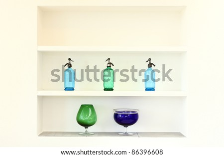 shelf with bottles and glasses colored