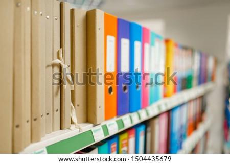Shelf with folders in stationery store, nobody
