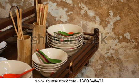 Shelf with oriental dishware. Wooden shelf with various Asian dishware hanging near crumbling wall in kitchen