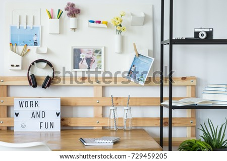 Shelf with photo camera in cozy workplace with board on white wall, headphones  #729459205