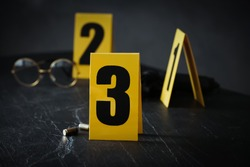 Shell casings and evidence marker on black slate table, closeup. Crime scene