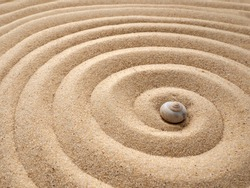 Shell in circles on the sand. Zen concept. Spiral in the sand