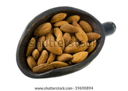 shelled almond nuts on a primitive, wooden, dark painted scoop, isolated on white