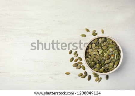 Shelled raw pumpkin seeds on wooden background, top view. Space for text #1208049124