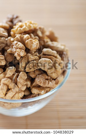 Shelled walnuts in glass plate on bamboo table cloth.