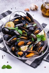 Shellfish mussels in copper bowl with lemon and herbs on white background with textile. Shellfish seafood.