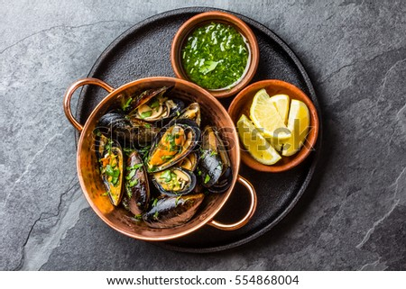 Shellfish Mussels in copper bowl with lemon and herbs sauce. Top view. #554868004